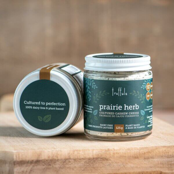 """Two Prairie Herb Cultured Cashew Cheese 125g jars, with one placed on its side to show the lid label, which says """"Cultured to perfection 100% dairy free & plant based"""""""
